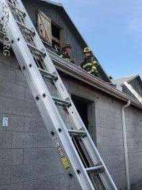 Firefighters Biondi & Carroll on the roof after clearing the attic.