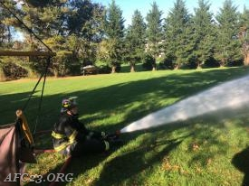 Firefighter Marzolf cooling the over-heated propane cylinder.