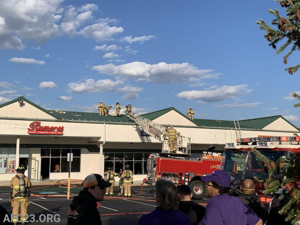 """Ladder 25 set up on the """"A"""" side with crews operating on the roof."""