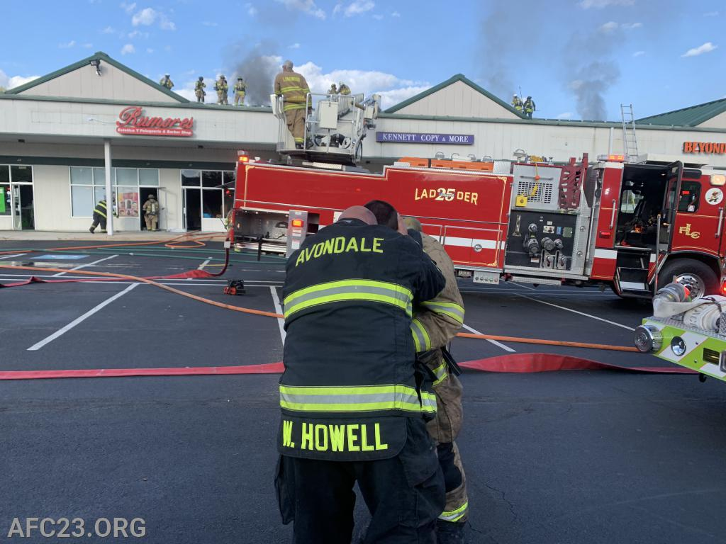 Firefighter Howell and Chief Hoseman Cole discussing their operation after knocking the fire.